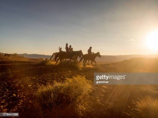group of young navajo siblings riding their horses bareback through the vast desert in northern arizona near the monument valley tribal park on the navajo indian reservation at dusk - apache stock pictures, royalty-free photos & images