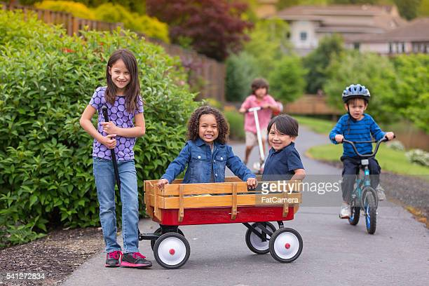 group of young neighborhood kids smiling and playing - toy wagon stock photos and pictures