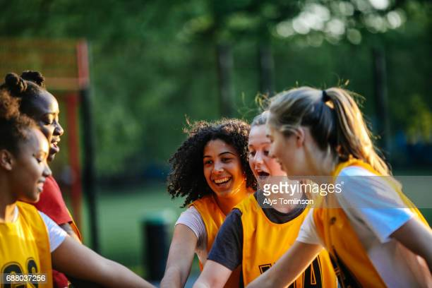 group of young netball players with hands together, before start of match on outdoor court - sports team stock pictures, royalty-free photos & images