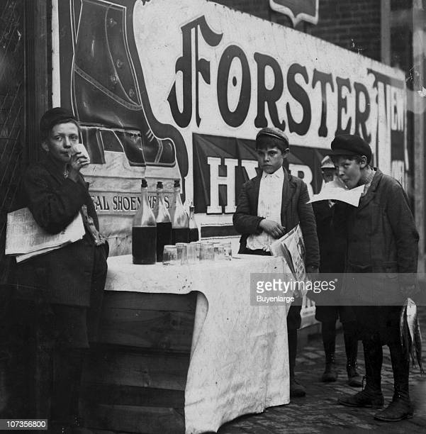 A group of young newsboys stand on a sidewalk around a crate where they purchase alcohol from several bottles Wilmington Delaware 1910
