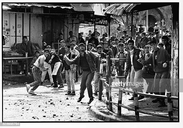 A group of young Palestinian men hurl stones at Israeli soldiers in the town of Khan Yunis in the Gaza Strip