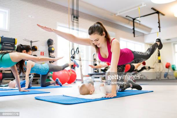 Group of young parents and babies doing fitness exercise in modern gym. Healthy lifestyle.