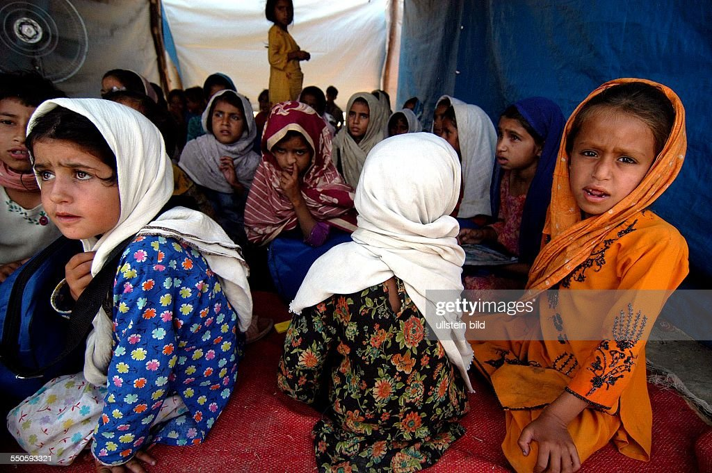 SHEICK SHAZAD CAMP, MARDAN, SARHAD PROVINCE, PAKISTAN - JUNE 24TH: A group of young Pashtun refugee girls are listening to their treacher during a reading session, June 24th 2009, in Pakistan. The sch : News Photo