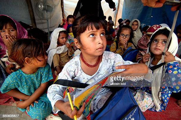 SHEICK SHAZAD CAMP MARDAN SARHAD PROVINCE PAKISTAN JUNE 24TH A group of young Pashtun refugee girls are listening to their treacher during a reading...