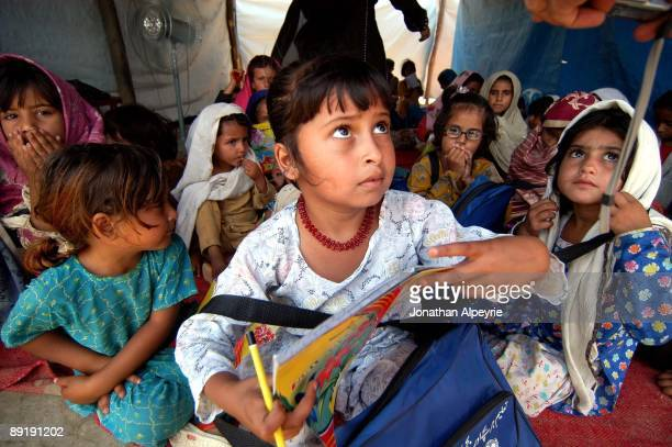 A group of young Pashtun refugee girls are listening to their treacher during a reading session June 24 in Pakistan