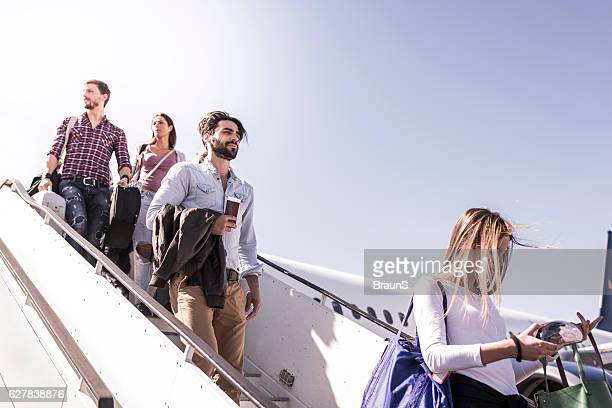 Group of young passengers disembarking the airplane.
