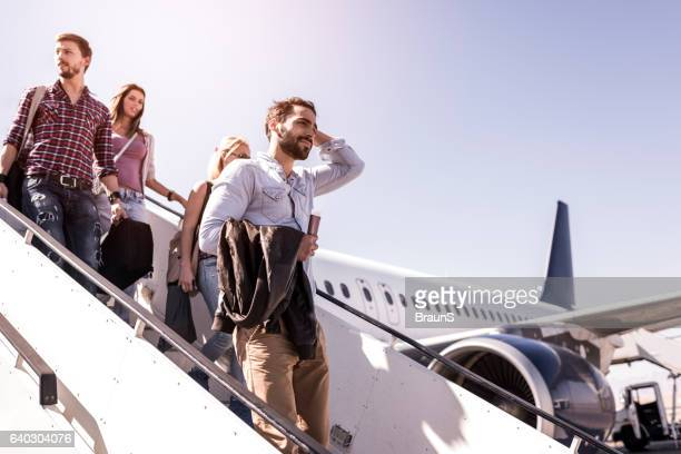 group of young passengers disembarking the airplane. - passagier stock-fotos und bilder
