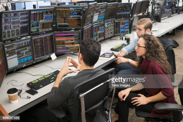 group of young people analyzing stock market data at trading desk - stock trader stock pictures, royalty-free photos & images