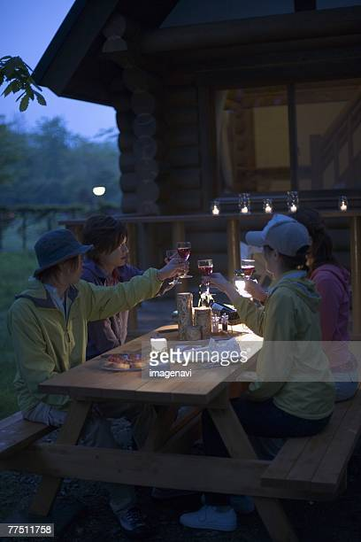 Group of Young People are Chatting on Campsite at Dusk