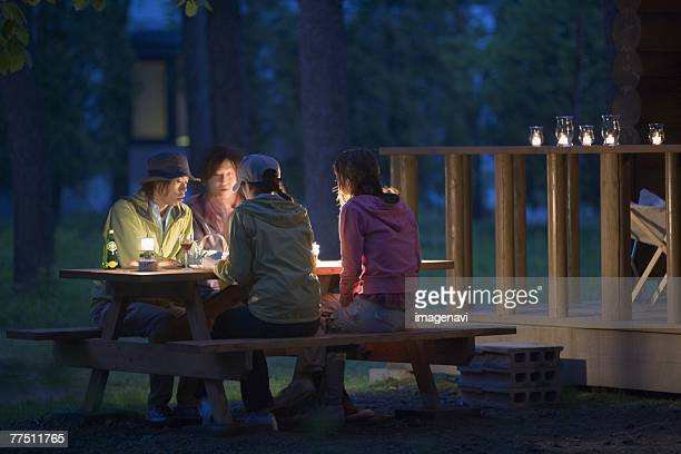 Group of Young People are Chatting on Campsite at Early Night