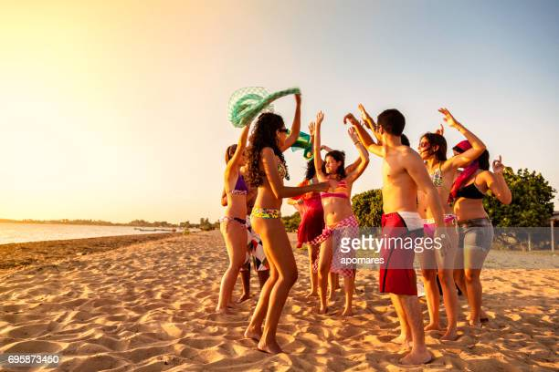 Group of young people at a hot summer tropical beach party at late afternoon