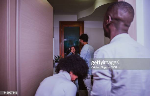 a group of young people celebrating and making party at home - chest kissing stock pictures, royalty-free photos & images