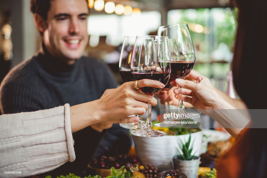 Group of young people celebrating Christmas party dinner with clinking glass of wine : Stock Photo