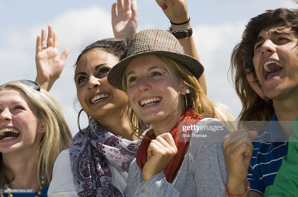 Group of young people cheering, outdoors : Foto stock