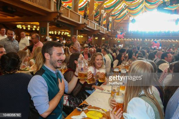 A group of young people cheering with beers on Day 12 of the Oktoberfest The Oktoberfest is the largest Volksfest in the world It will take place...
