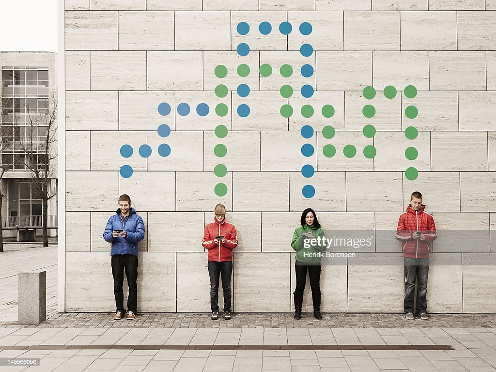 A group of young people standing against a wall using their mobile phones. They are connected with dots.