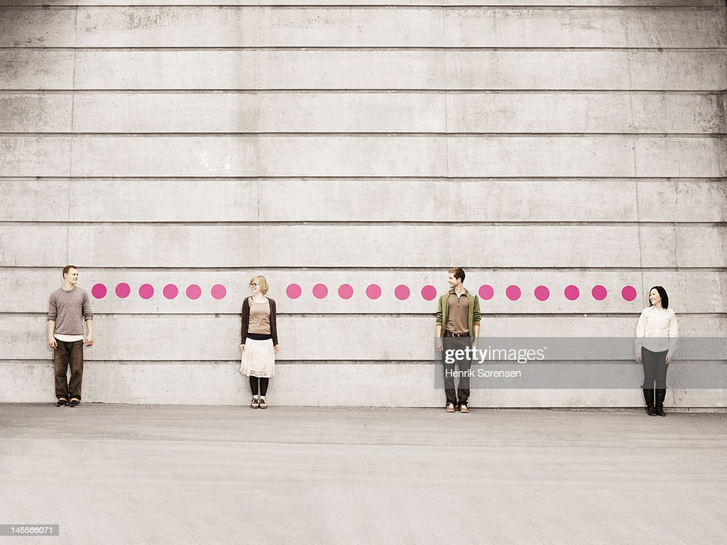 Four young people looking at each other, standing against a wall connected with dots.