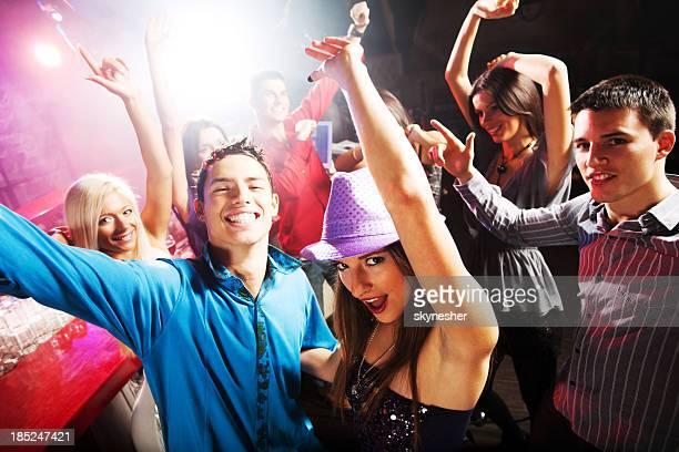 Groupe de jeunes gens danser dans la discothèque.