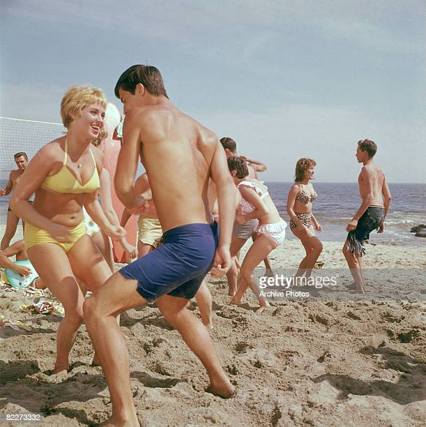 A group of young people dancing to rock 'n' roll on the beach circa 1960