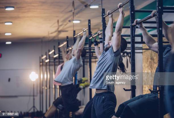 group of young people doing chin-ups in a gym - leisure facilities stock pictures, royalty-free photos & images