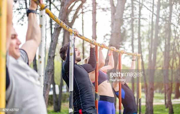 group of young people doing pull ups outdoors - sports team event stock photos and pictures