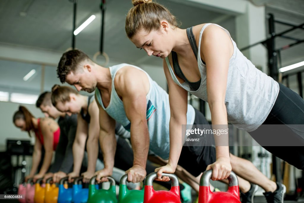 Group of young people doing push-ups on kettlebells : Stock Photo