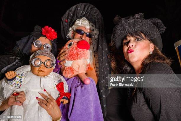 Group of young people, dressed up in mourning clothes and smiling, partying in the streets during the funeral procession Burial of the Sardine, the...