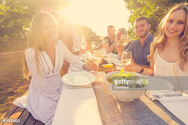 Group of young people eating outdoors.