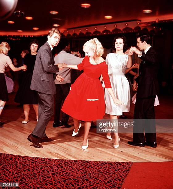 Group of young people enjoy an evening at the dance hall Couples dance together on the polished wooden floor under coloured lights wearing the latest...