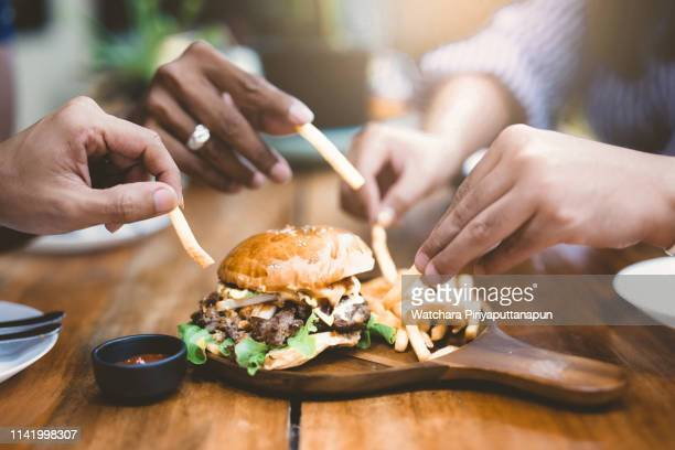 group of young people enjoying home party with hamburger and french fries. - unhealthy living stock pictures, royalty-free photos & images