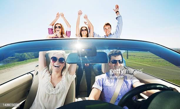 Groupe de jeunes gens appréciant dans une voiture décapotable en voiture.