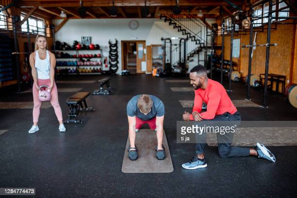 group of young people exercising at the gym - small group of people stock pictures, royalty-free photos & images