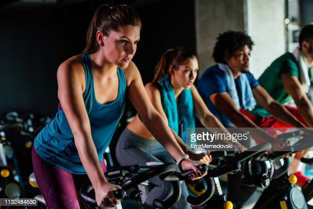 group of young people exercising on exercise bikes at gym - roda imagens e fotografias de stock