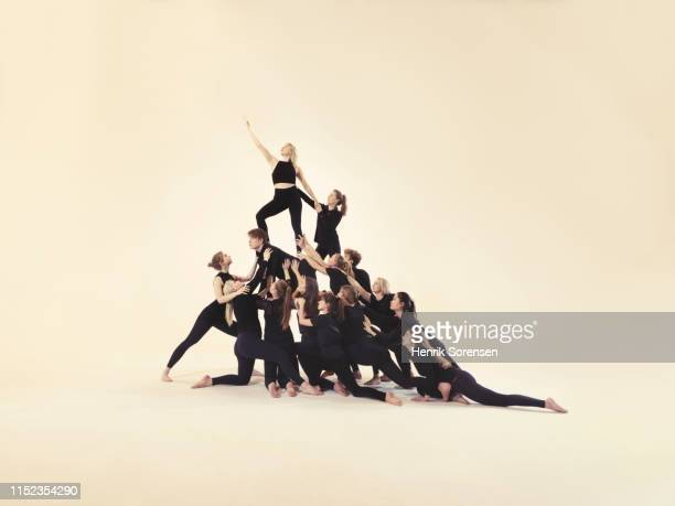 group of young people forming a pyramid - pyramid stock pictures, royalty-free photos & images