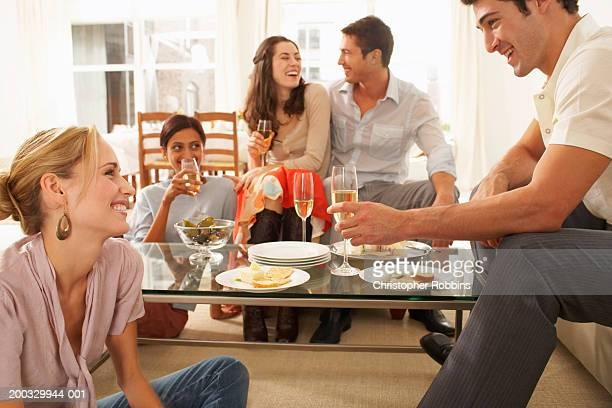 Group of young people gathered around coffee table drinking champagne