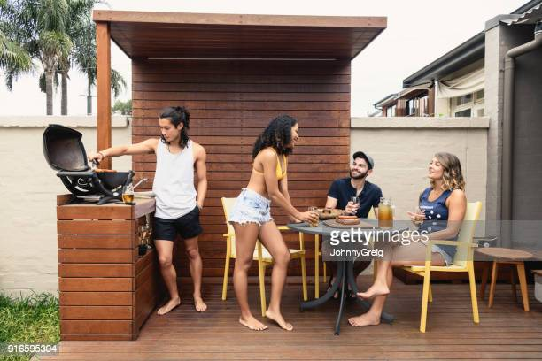 group of young people having bbq on decking with alcoholic drinks - deck stock pictures, royalty-free photos & images