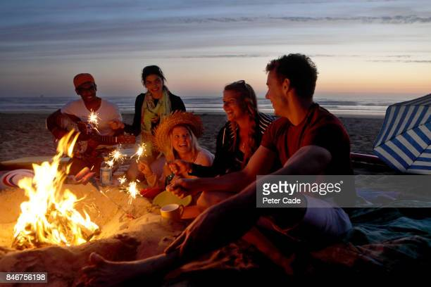 group of young people having fire on beach in the evening - キャンプファイヤー ストックフォトと画像