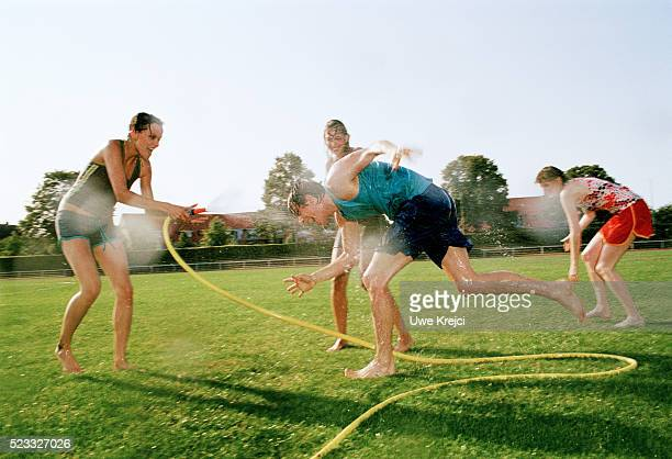 Group of Young People Having Water Fight on Lawn