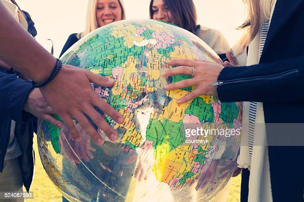 group of young people holding a world globe - emigration and immigration stock pictures, royalty-free photos & images