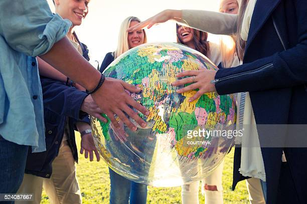 Group of young people holding a world globe