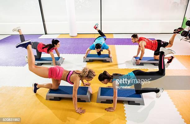 Groupe de jeunes personnes à la salle de sport au cours de étape entraînement.
