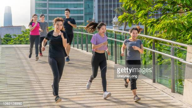 屋外kl都市の背景をジョギングする若者のグループ - extra long ストックフォトと画像