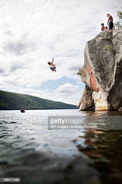 A group of young people jumping from a height from a cliff into the still waters of a lake.
