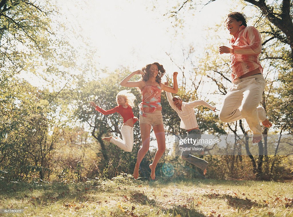 Group of Young People Jumping in the Air in a forest Clearing : Stock Photo