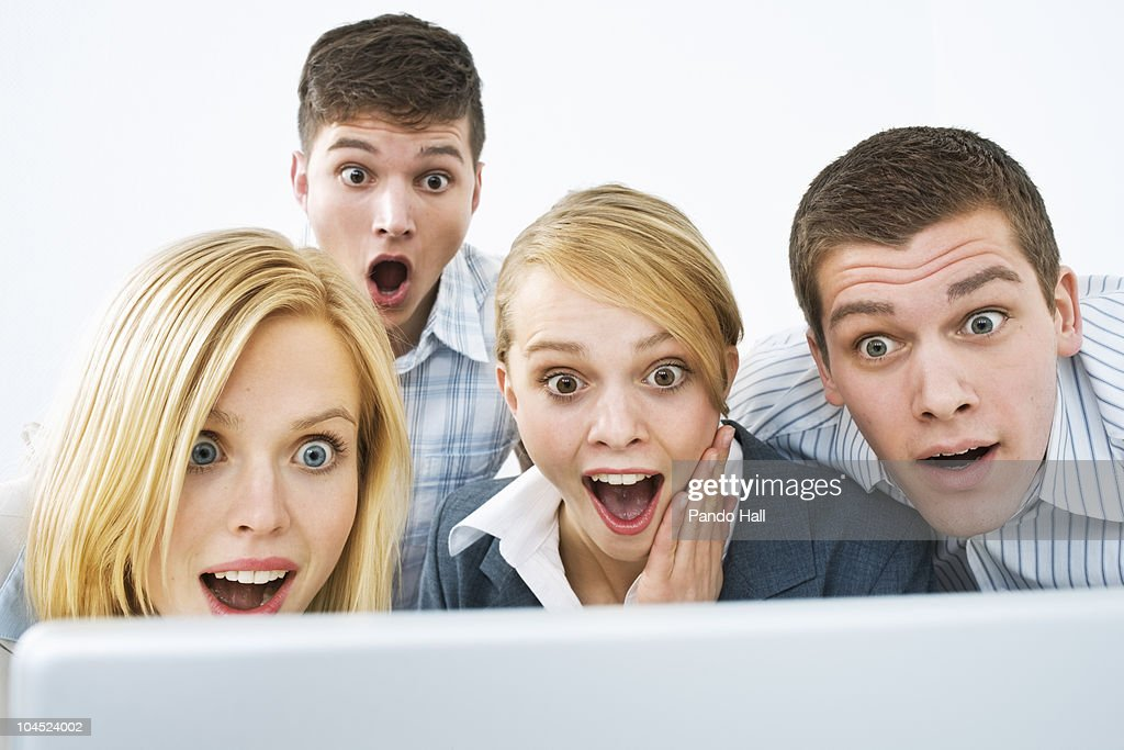 Group of young people looking on laptop, laughing : Stock Photo