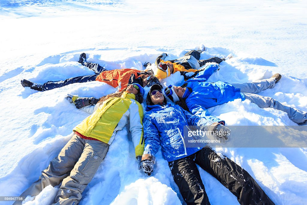 Group of young people making snow angels : Stock Photo