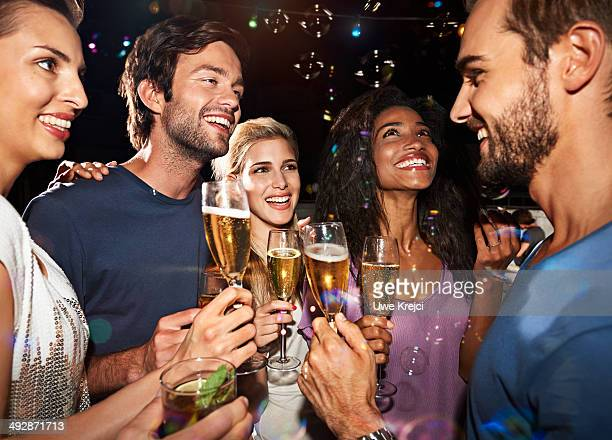 Group of young people making toast at party