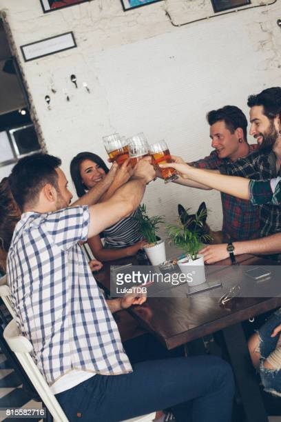 Group of young people making toast with beer at the bar