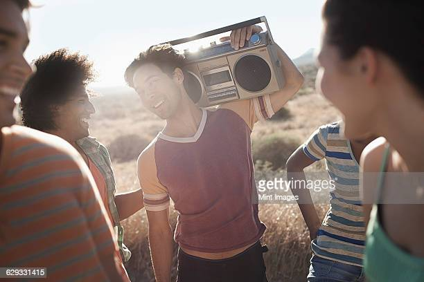 Group of young people, men and women walking on the open road with a boombox.