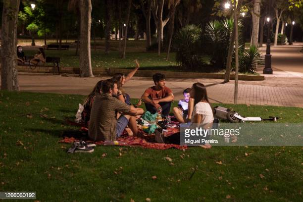 Group of young people not wearing face masks gather socially at night in the Debod Temple park on August 12 in Madrid, Spain.